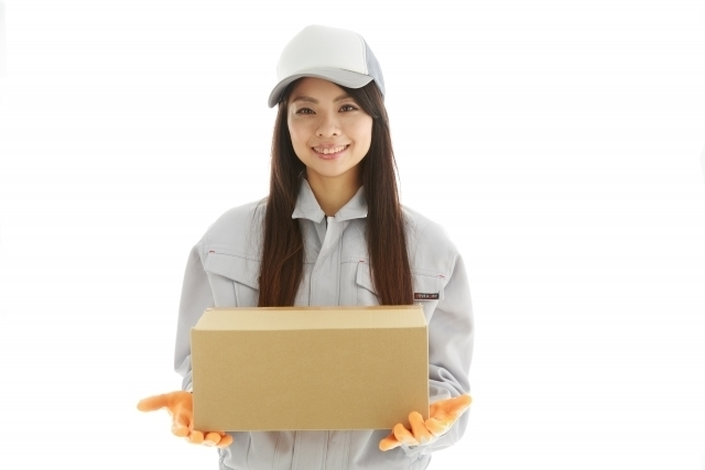 荷物を届けに来た笑顔の女性宅急便スタッフ