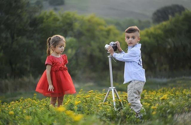 花畑で少女の写真を撮ろうとする少年