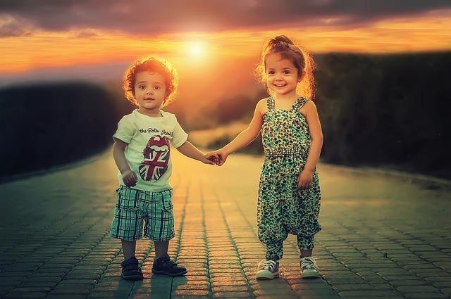 夕日を背に手をつないで立つ幼い姉弟