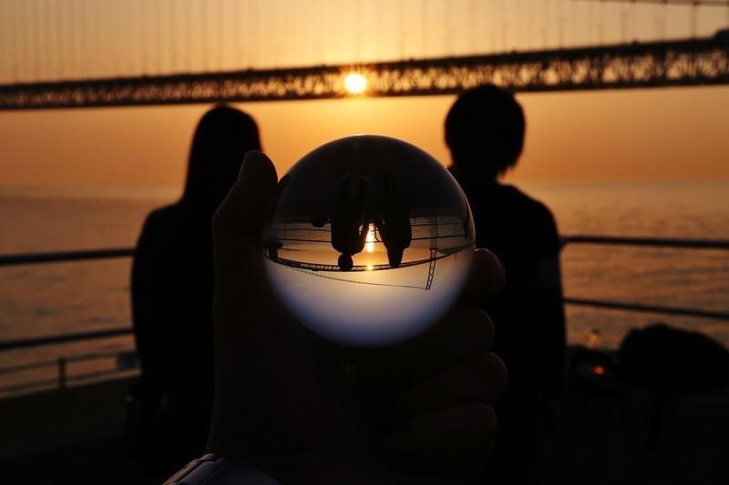 浜辺で夕日を眺める恋人同士を後ろから水晶玉で眺める