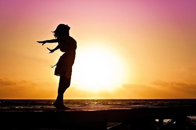 海に沈む夕日を背景にした逆光の女性