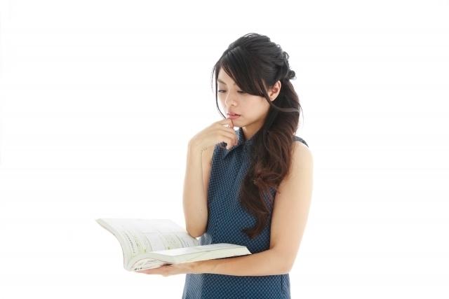 本を片手に考える女性