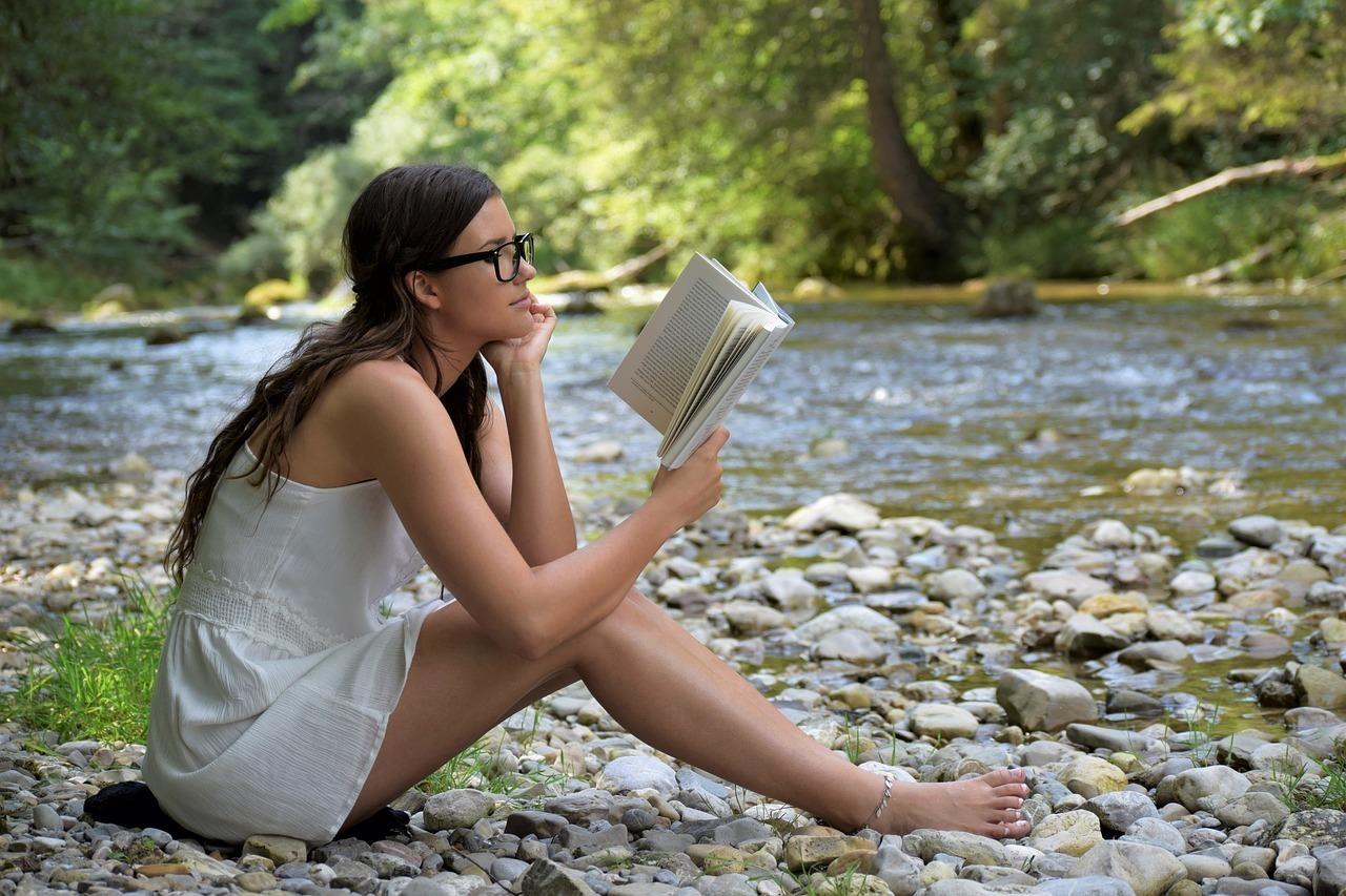 川辺で読書をする女性