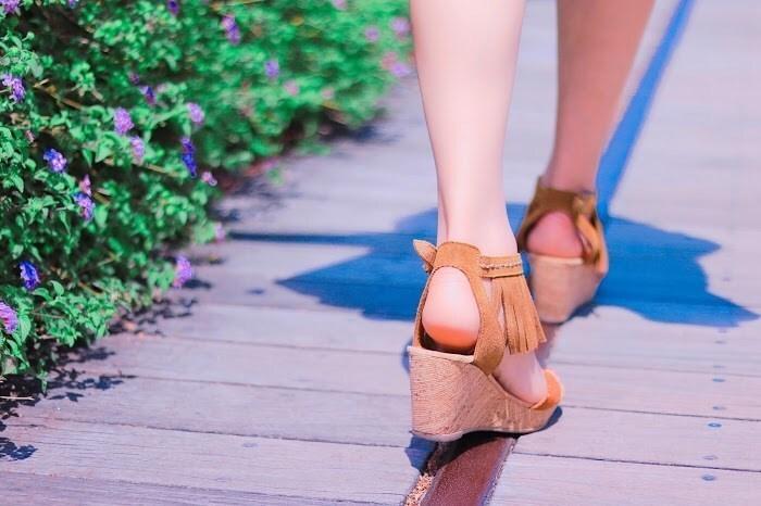 女性の足元と花々