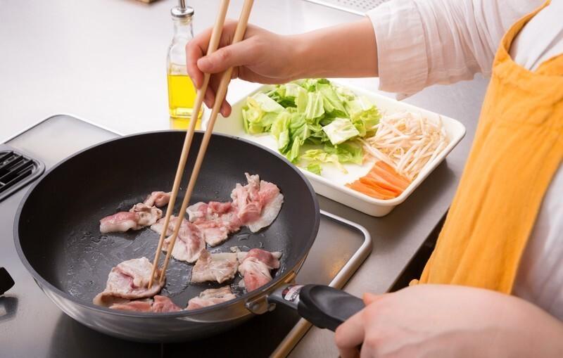 フライパンで豚肉を炒める光景