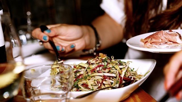 女性がレストランで食事する光景