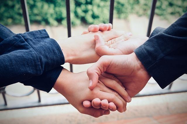 両手で握手し合う2人