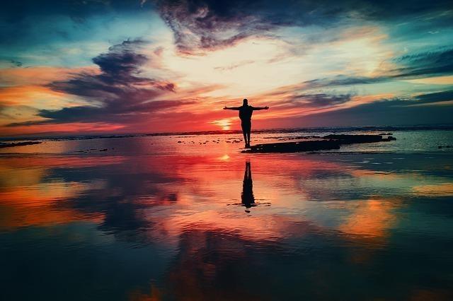 夜明けのウユニ塩湖で両手を広げる男性