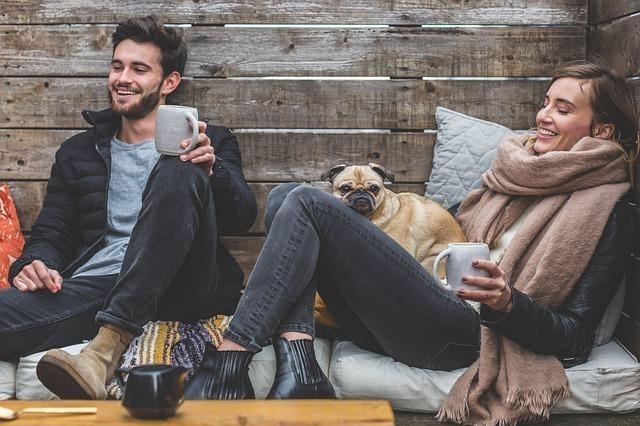 温かい飲み物を飲みながら愛犬とくつろぐ男女