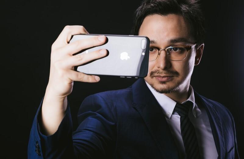 男性が携帯で写真を撮っている