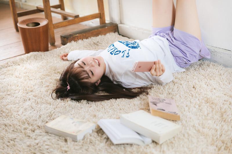 読書を使用としてスマホを見ている女の子