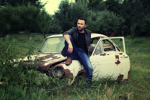 ボロボロの車のボンネットに座る男性