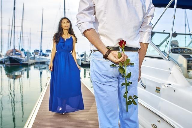 青いワンピースを着た女性にバラを私て驚かそうとしている男性