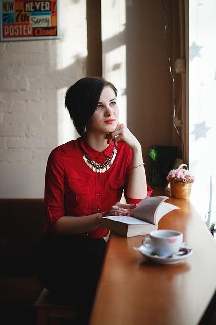 カフェの窓際で思考を巡らす女性