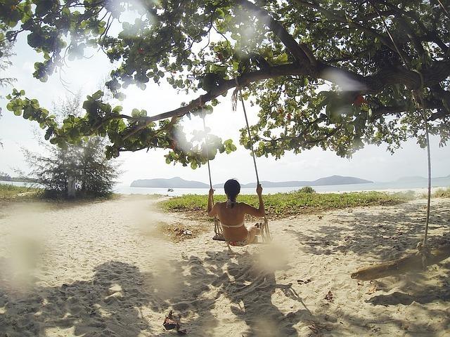 海辺の木に作ったブランコに乗り自由な時間を楽しむ女性