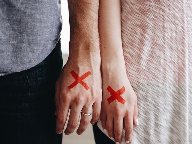 左手の薬指に指輪をした男性と女性の手の甲に罰印がついている画像