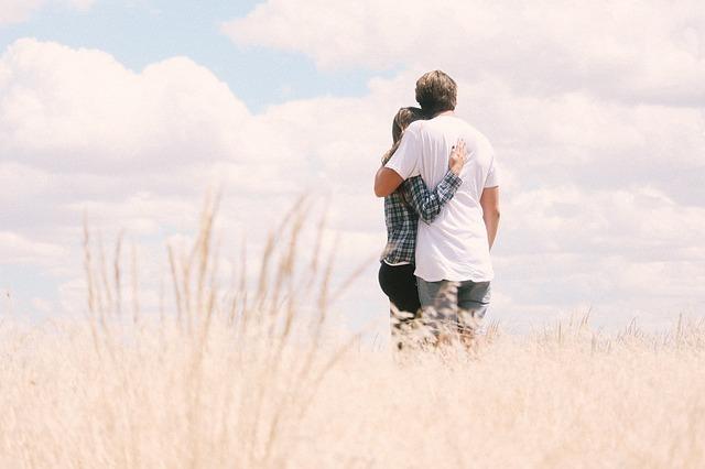秋の野原で優しく抱き合う男女