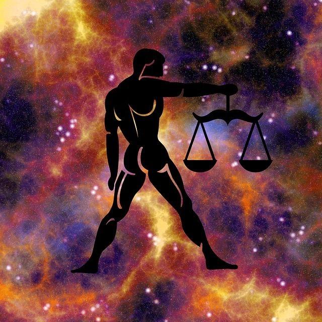 宇宙に浮かぶ天秤を掲げた男性の後ろ姿