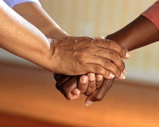 オレンジの袖の人の手を包み込む手