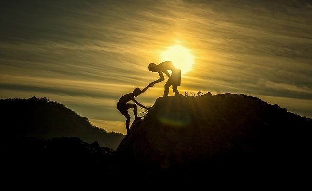 崖を登るのを助ける人