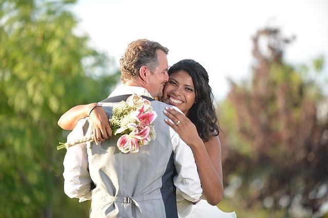 白人男性と黒人女性の結婚式での幸せそうに抱き合うワンシーン