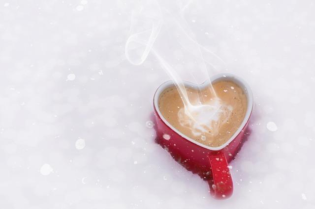 雪の中に埋もれて湯気の立つ飲み物の入った赤いハートのマグカップ