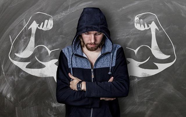 うつむきがちに腕を組んで立つ男性。後ろには筋肉が盛り上がった両腕の絵。