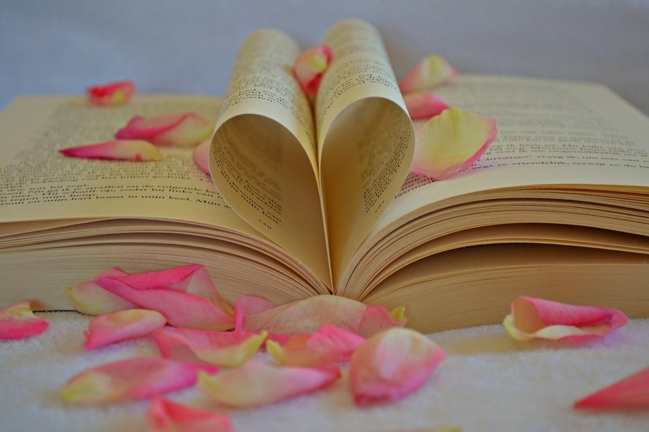 ページでハートを模った本と周りに散らばる花びら