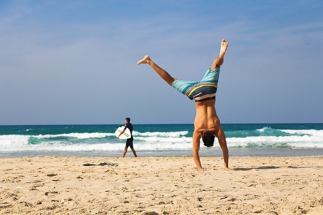 海岸で水着姿のまま逆立ちする男性