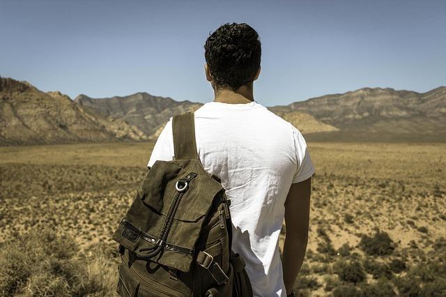 リュックを背負い荒野に立つ男性の後ろ姿