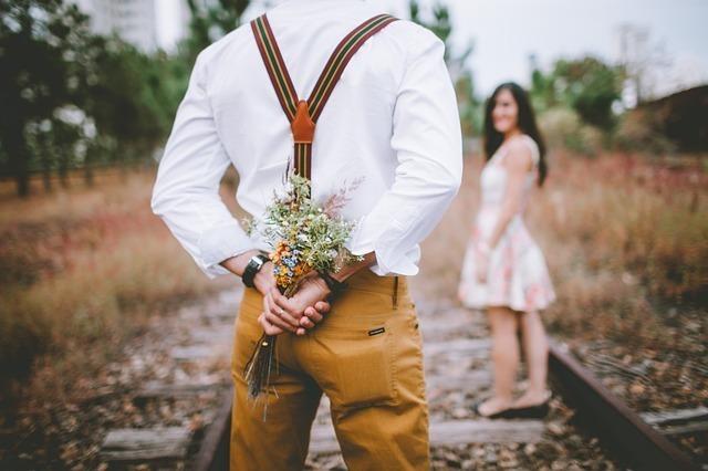 女性の前で花を後ろに隠す男性