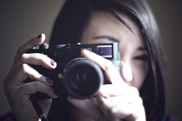 カメラをのぞき込む女性