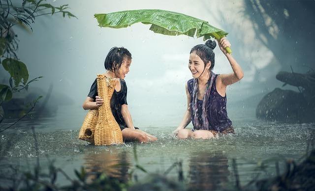 雨の中で母親が子供を守る光景