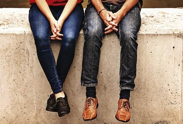 コンクリートの塀の上に並んで座る男女の腰から下