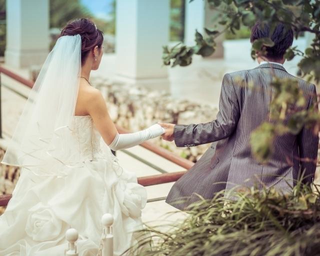 結婚式で新婦の手を引いてエスコートする新郎
