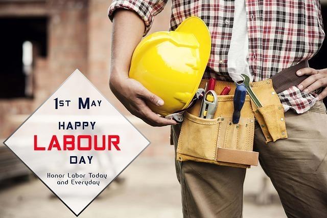 労働者をイメージして腰に工具などを下げヘルメットを抱えた男性