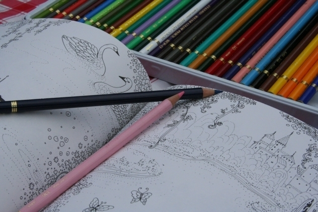 色とりどりの色鉛筆と広げられた大人の細かい塗り絵の一ページ