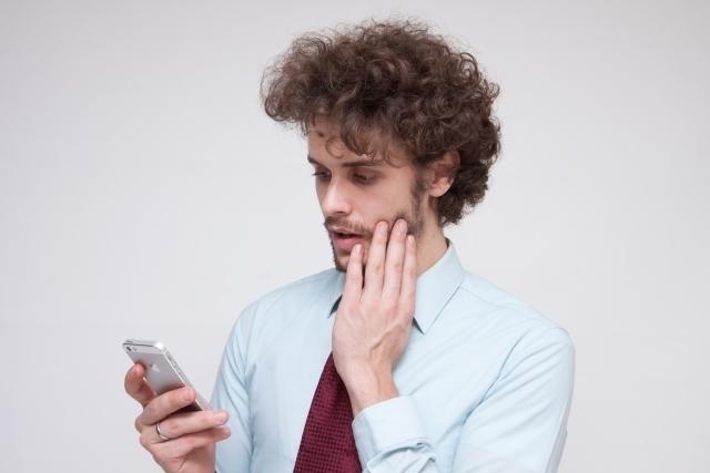 頬に手を添え携帯電話の画面を見る男性