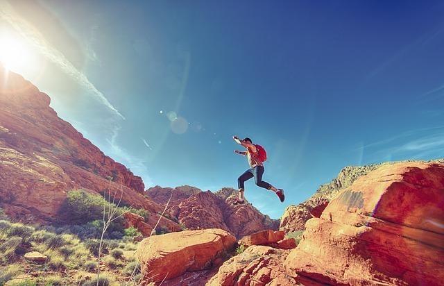 岩から岩へ飛び渡る元気溢れた男性