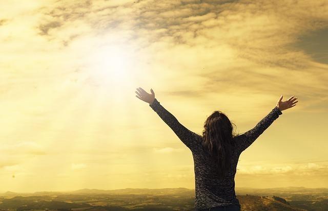 高台で太陽に向かって両手を広げる女性