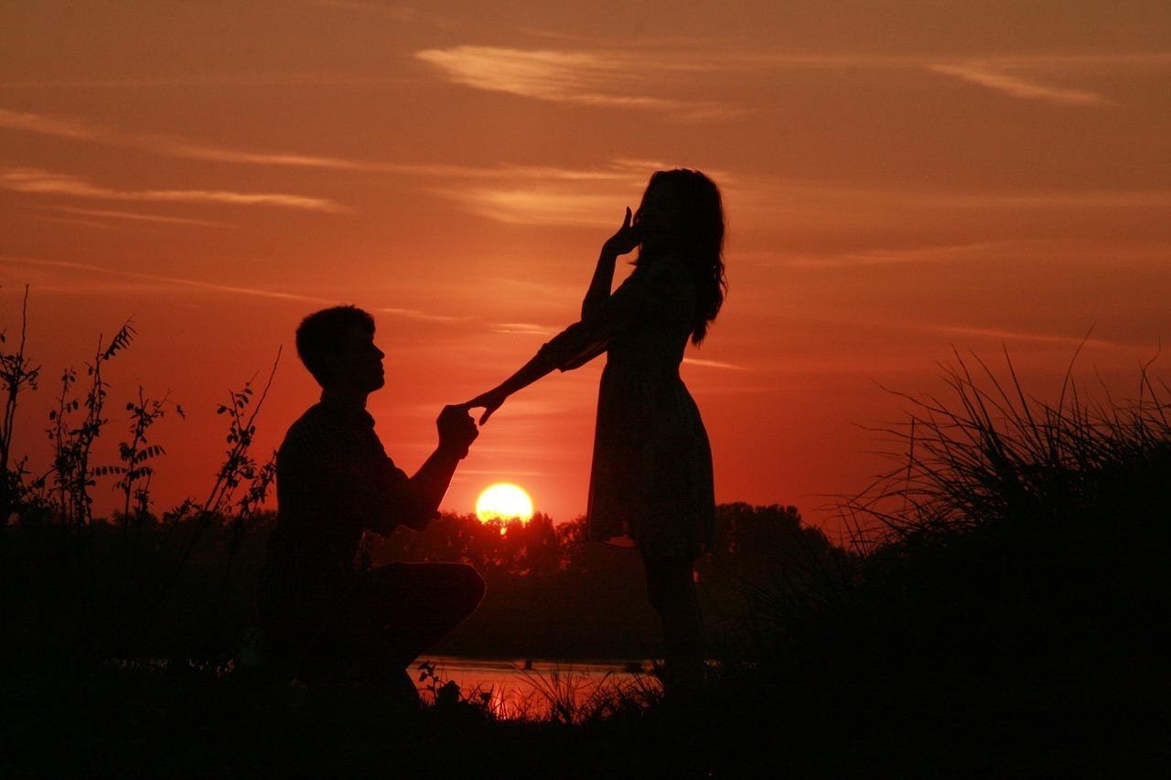 夕陽の中跪いて女性にプロポーズする男性