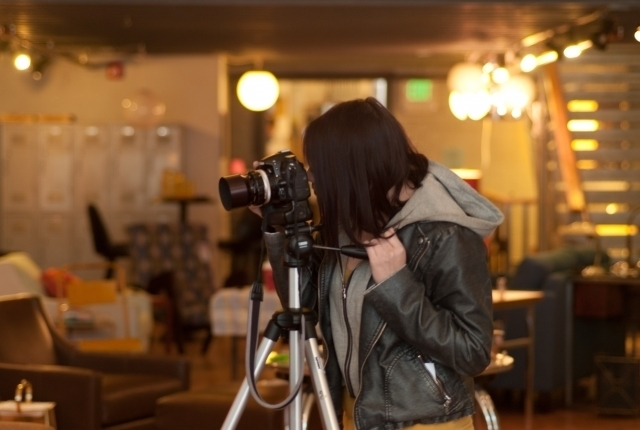 カメラで店内を撮影している女性の画像