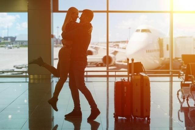 空港のロビーで抱き合うカップルの画像