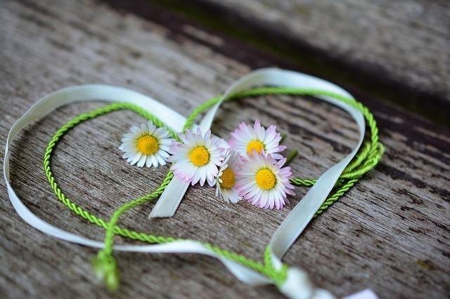 リボンでハートをかたどり小花を飾る画像