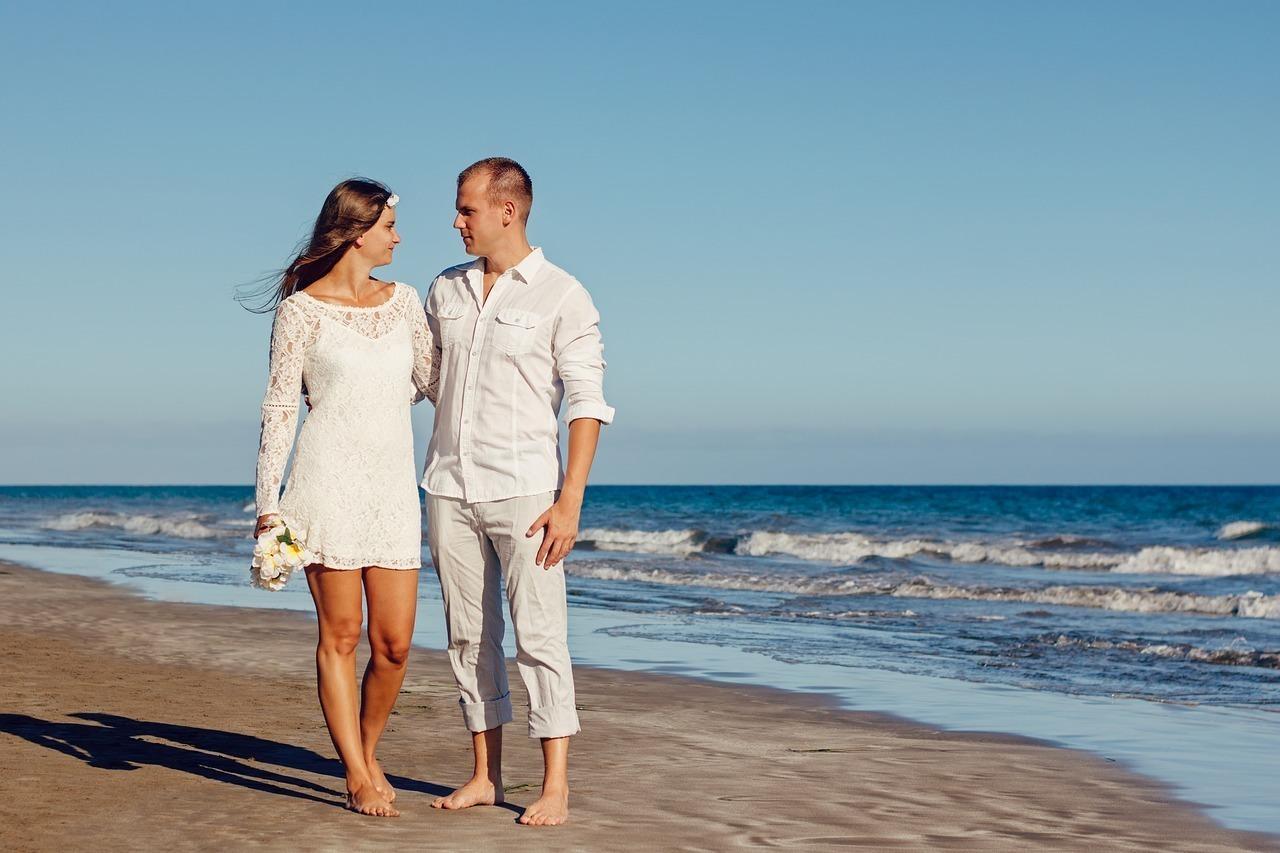 海辺を見つめ合い並んで歩くカップル