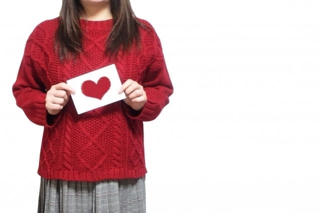 赤いハートのカードを持った女性の画像