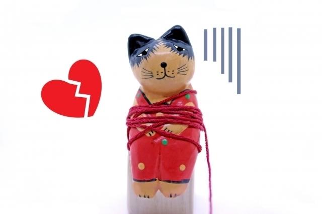 猫の人形が毛糸でぐるぐる巻きにされて困っている画像