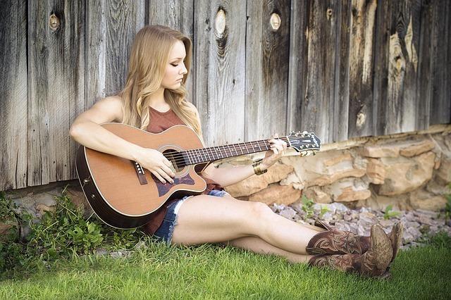 ウェスタンブーツの若い女性が芝生に座ってギターを弾いている画像