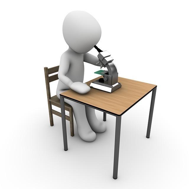 椅子に腰かけて机の上の顕微鏡をのぞき込む画像