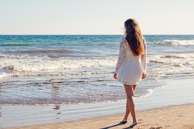 波打ち際に近寄る女性の後ろ姿
